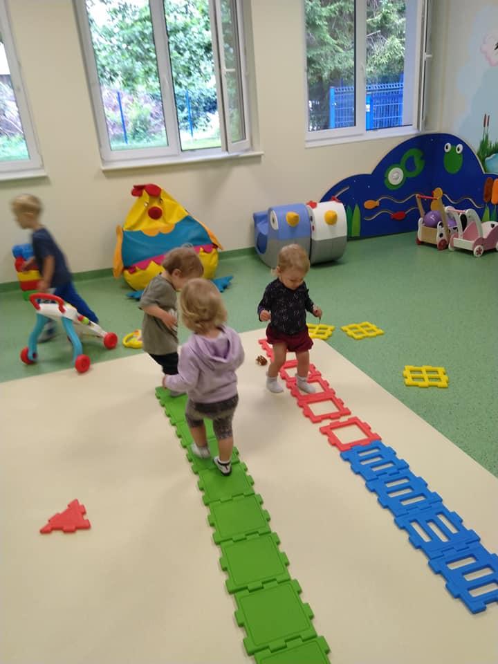 Dzieci w towarzystwie opiekunek rozwijają swoje umiejętności motoryczne.